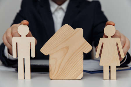 Broker holds wooden figures of young family. Close-up. Purchase of house concept