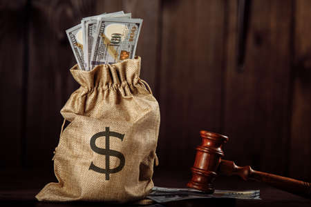Dollar money bag and judges gavel. Lawyer services. Protection of rights Фото со стока