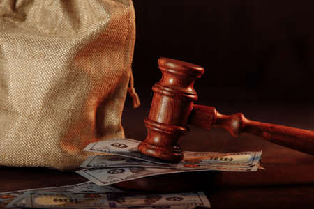Money bag and judges gavel close-up in dollar banknotes