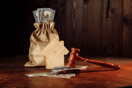 Bag of money, house and judge gavel. Taxes on real estate, payment concept