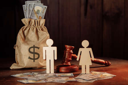 Bag of money, dollar banknotes, people and the judges hammer. The concept of divorce Фото со стока