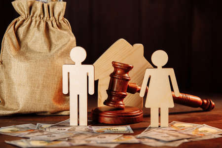 The division of property and divorce concept. Bag of money, house, people and the judges hammer Фото со стока