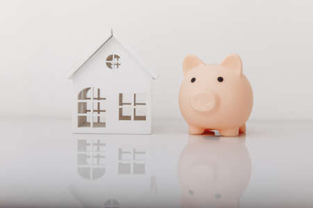 Piggy bank and house model. Savings and banking concept Zdjęcie Seryjne