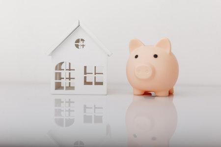 Piggy bank and house model. Savings and banking concept Фото со стока
