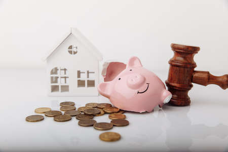 Wooden gavel, broken piggy bank and house model with coins. Real estate auction concept