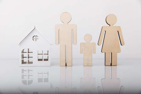 Wooden model of house and family isolated on white background. Close-up Фото со стока