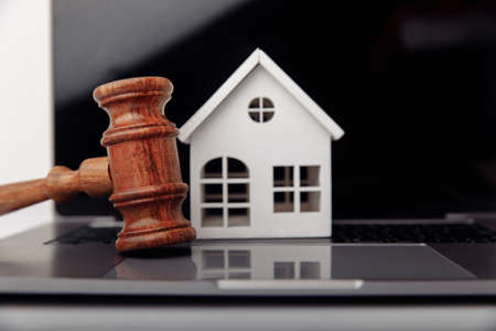 Wooden gavel and house on a laptop close-up. Real estate mortgage auction Zdjęcie Seryjne