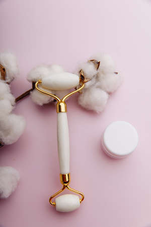 Face care and anti-aging concept. Stone roller with cream on pink background. Vertical image Zdjęcie Seryjne