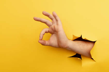 Hand gesture ok through a hole in yellow background