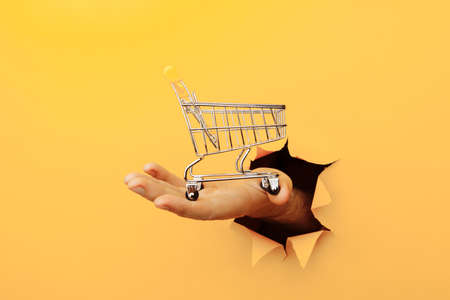 Male hand holds through a hole a mini grocery shopping trolley on a yellow paper background. Sales or shopping concept Фото со стока