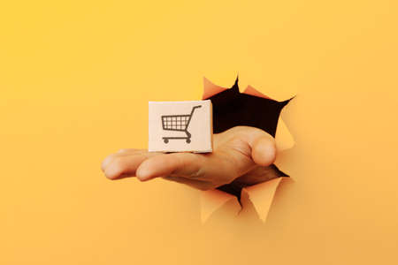 Hand with a delivery box through a yellow paper hole Zdjęcie Seryjne