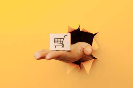 Hand with a delivery box through a yellow paper hole Фото со стока