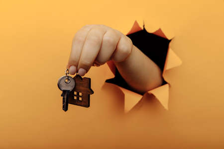 Hand with house keys through a hole in yellow paper wall. close-up. House sale and rent concept Фото со стока