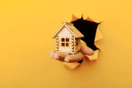Hand with a wooden house model through a yellow paper hole