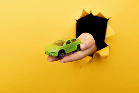 Female hand with house car through a rip in yellow paper wall. Sale and rent concept
