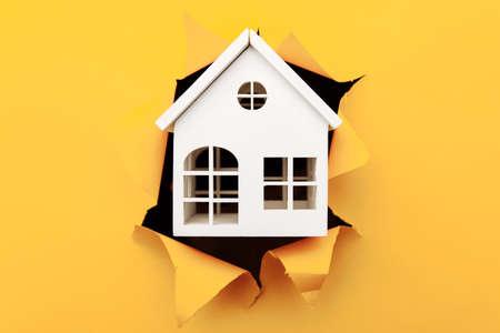 White wooden house model through a yellow paper hole close-up Фото со стока - 167234632