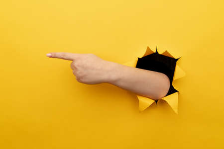 Female left hand pointing to the right through a yellow background.