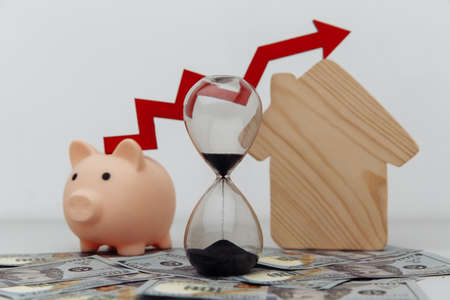 Piggy bank, hourglass with arrow up and wooden house models on dollar cash close-up Фото со стока