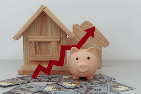Piggy bank with arrow up and wooden house models on dollar banknotes, Saving or loan for buy house or real estate concept Фото со стока