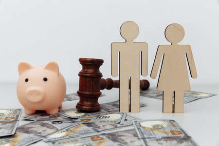 Wooden family figures, gavel and pink piggy bank on dollar banknotes, savings and divorce concept Фото со стока