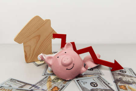 Investment and bankruptcy concept. Real estate. Broken piggy bank and red arrow down with wooden house on dollar banknotes isolated on white Фото со стока