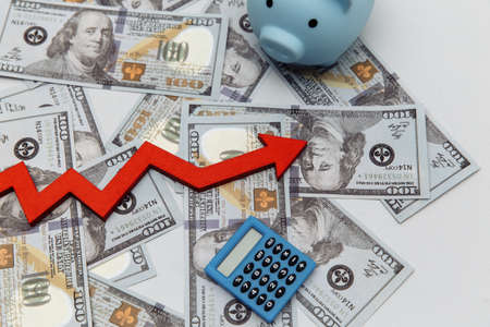 Investment concept. Piggy bank and arrow up on dollar banknotes