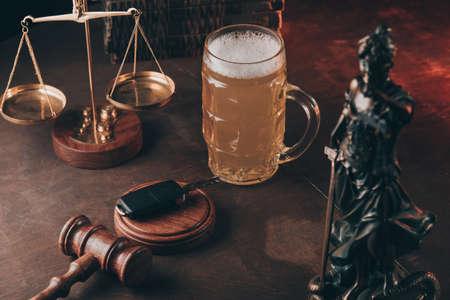 Glass with beer, lady of justice and wooden gavel with car keys on a table