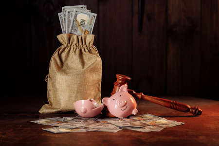 Broken piggy bank with money bag and judge gavel. Investment and bankruptcy concept