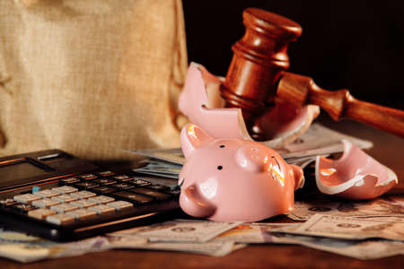 Broken piggy bank with money bag and judge gavel close-up. Economy concept