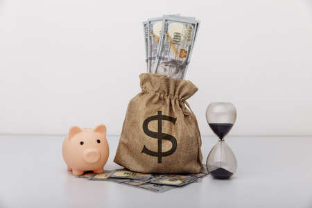 Hourglass with money bag and piggy bank on white background. Finance saving and investment concept