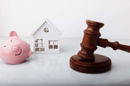 Wooden gavel, broken piggy bank and house model isolated on white. Auction and bankruptcy concept 版權商用圖片