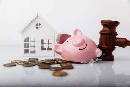 Wooden gavel, broken piggy bank and house model with coins close-up. Auction and bankruptcy concept