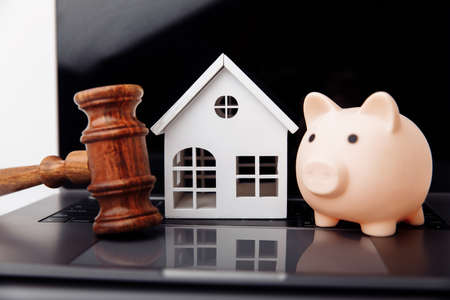 Wooden gavel, piggy bank and house on a laptop. Online auction 版權商用圖片