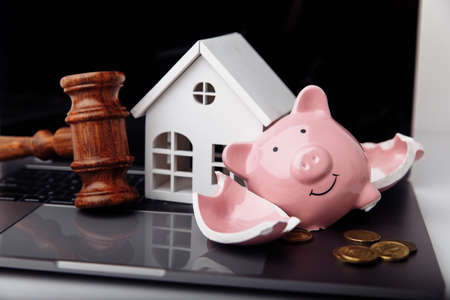 Wooden gavel, broken piggy bank and house. Real estate auction concept 免版税图像