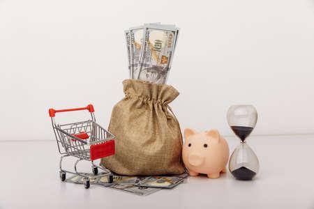 Dollar money bag, ohurglass and a shopping cart