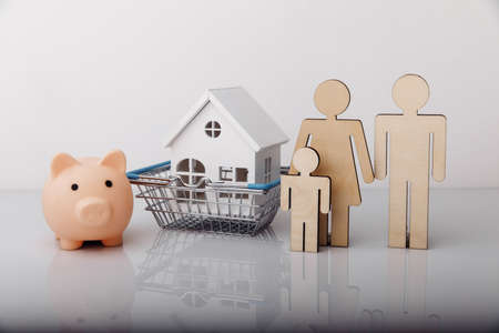 Small model of house, piggy bank and family isolated on white background 版權商用圖片