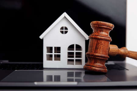 Wooden gavel and house on a laptop close-up. Online auction concept