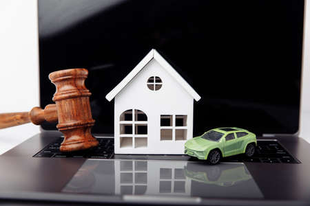 Wooden house, car and judge gavel. Purchase, sale of real estate 版權商用圖片