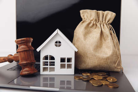Wooden gavel, broken piggy bank and money bag. Real estate auction concept