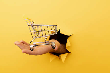 Hand holds through a hole a mini grocery shopping trolley on a yellow paper background. Sales or shopping concept