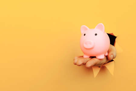 Hand with a piggy bank through a yellow paper hole. Financial and business concept