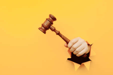 Hand holding a judges gavel through torn yellow paper wall. Law and courts, triumph of justice 版權商用圖片