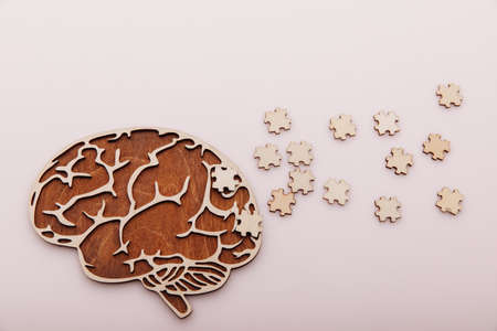 Alzheimers disease and mental health concept. Brain and wooden puzzle on a pink background