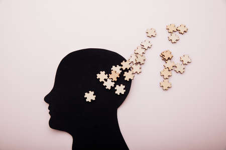 Head of man and wooden puzzle. Alzheimers disease, dementia and mental health concept