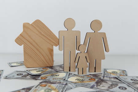 Wooden figures of family with house. Purchase or sale concept 版權商用圖片