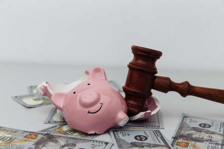 Broken piggy bank and judge gavel. Bankruptcy or crisis concept