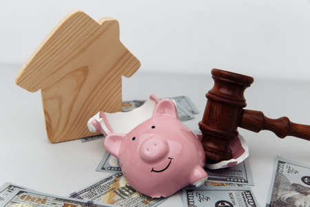 Broken piggy bank, house and judge gavel. Bankruptcy and investment concept