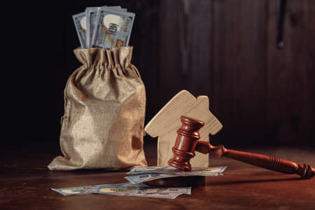 Real estate auction concept, money bag with cash house and judge gavel 版權商用圖片