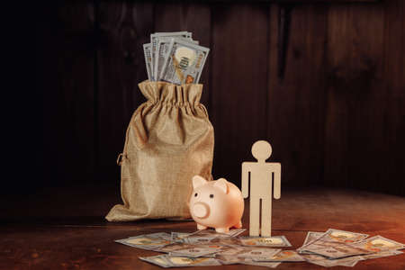 Bag of money, piggy bank and figure of man The concept of business and investment