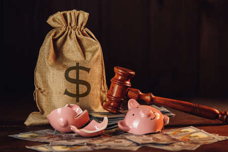 Broken piggy bank with money bag and judge gavel. Economy concept 版權商用圖片